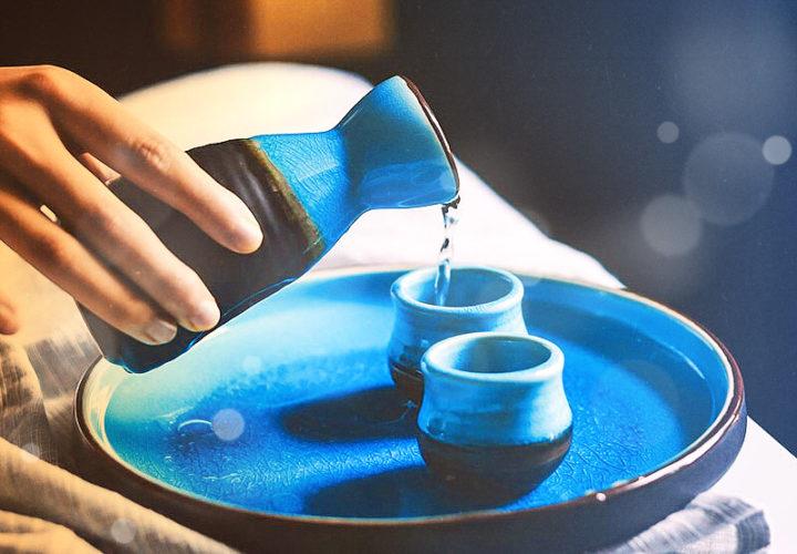 разлив саке в две чаши голубого цвета